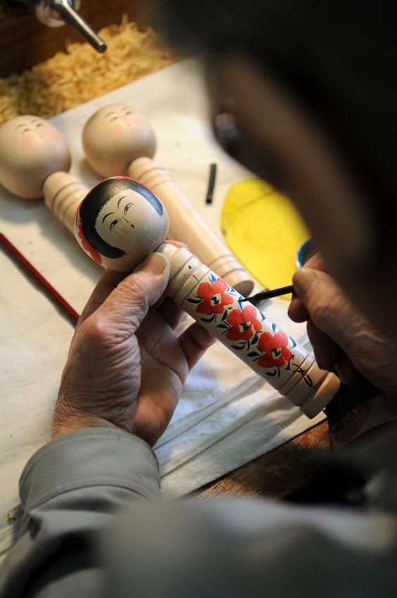 Mr. Aida drawing flowers in the body in one of his kokeshis with a Japanese brush and black ink.Mr. Eiji Aida was a very famous kokeshi artisan with a shop in the heart of Tendo town. He passed away a few years ago, but his kokeshis are very impressive still. Tendo. Yamagata.